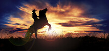 Silhouette Of Cowboy Rearing His Horse At Sunset