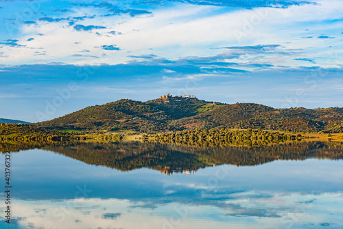 Reflection of a castle and its medieval fortress on the banks of the Guadiana river, very close to Badajoz between the border of Spain and Portugal, Europe.