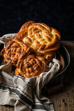 Three Homemade Braided Yeast Breads On Towel In Round Metal Tray On Wooden Table On Dark Blue Background.