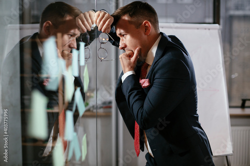 Obraz Businessman in conference room use sticky notes on glass wall. Handsome businessman making a business plan.. - fototapety do salonu