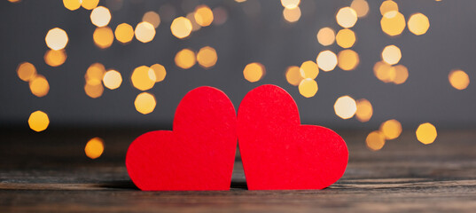 pair of red hearts on lights background, love and valentine concept on a wooden table