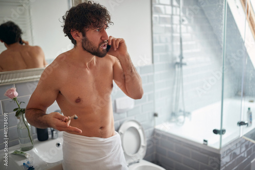 Fototapeta Angry topless man fighting while brushing teeth
