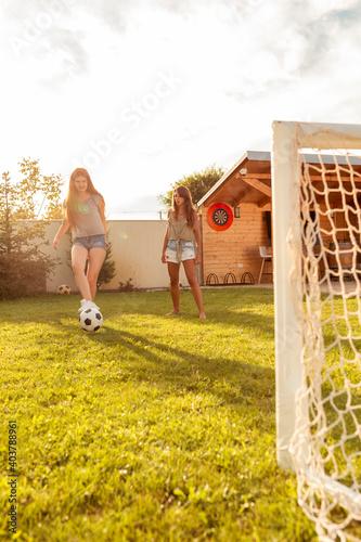 Obraz Young friends having fun playing football in the backyard - fototapety do salonu