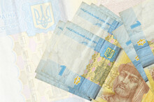 1 Ukrainian Hryvnia Bills Lies In Stack On Background Of Big Semi-transparent Banknote. Abstract Presentation Of National Currency