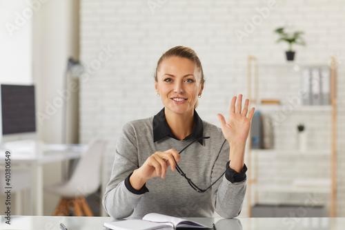 Fotografia Happy young woman sitting at desk, waving hand at camera