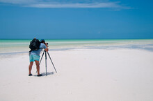 The Photographer With His Camera On His Trestle Takes Landscape Photographs At Low Tide On The Island Of Holbox, Mexico. In The Background The Blue Sky And A Heron On The Sea