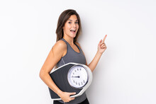 Teenager Brazilian Girl Holding A Scale Over Isolated White Background With Weighing Machine