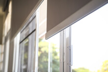 Details Of White Fabric Roller Blinds On The Plastic Window In The Living Room.