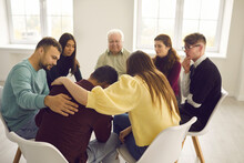 Compassion, Help And Dealing With Problems In Group Therapy Session At Rehab Center. Diverse Young And Senior People Sitting In Circle, Supporting And Comforting Crying, Stressed, Desperate Man