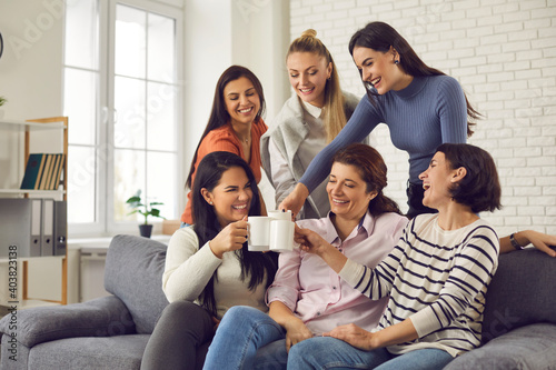 Obraz Group of happy young women having fun and enjoying time together. Smiling friends or colleagues sitting on sofa at home or in office, laughing at funny joke, clinking cups and drinking coffee or tea - fototapety do salonu