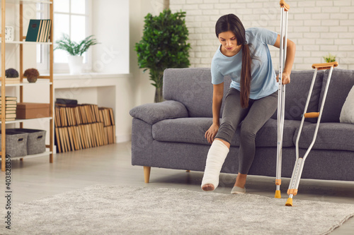 Canvas Print Young woman with broken leg in plaster cast trying to stand up from sofa and walk with crutches in living-room