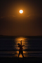 Women Strikes A Pose Silhouetted Against Harvest Moon Highlights