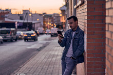 Young Man Writes On His Phone Leaning Against A Wall