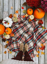 Overhead View Of Woman's Feet On Plaid Scarf Surrounded By Fall Items.