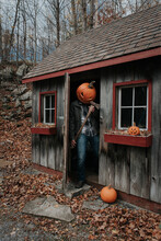 Man Wearing Scary Carved Pumpkin Head In Shed With Axe For Halloween.