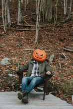 Man Wearing Scary Pumpkin Head At Halloween Sitting On Dock With Beer.