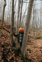 Man Wearing Scary Carved Pumpkin Head In The Woods For Halloween.