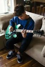 Teen Boy Practicing Electric Guitar At Home