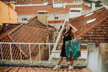 Female Artist Holding Canvas While Standing On Tiled Roof With View