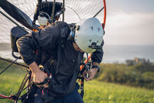 Young Man, Wearing A White Helmet With An Action Cam On It, Gets Ready To Fly With The Powered Paragliding ( PPG ) , And Fastens His Belt. In The Background The Ocean.
