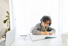 Boy Writing And Drawing Home School Work By Dining Table At Home