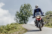Motorcyclist Driving On A Mountain Road. Adventure Concept