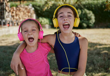 Little Girls Listening To Music And Smile With Yellow And Pink Headphones In A Garden. Happiness Concept