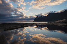 Reflection Of Okshornen Mountain Peaks In Tidal Pool At Tungeneset Viewpoint, Senja, Norway