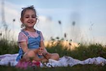 Little Girl Sitting On A Blanket Outside