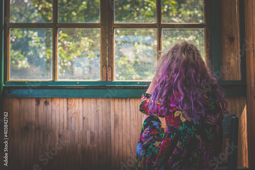 girl in beautiful colorful dress and pink hair in magic afternoon atmosphere loo Fototapet