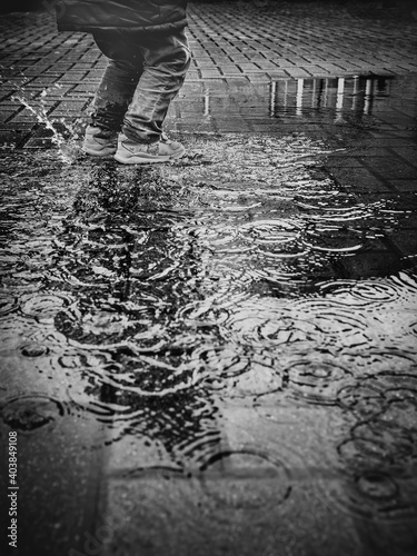 Fotografie, Obraz Vertical greyscale shot of a kid jumping in a puddle on a rainy day