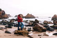 Couple Walking Along The Beach, Travel Romantic Vacation Outdoors Healthy Lifestyle Man And Woman Together Enjoying The Ocean And Rocks Landscape.