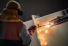Demolition Construction Worker Using A Flame Torch To Cut Up Heavy Machinery