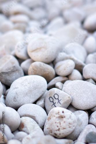 Fototapeta Kamyk z parą symboli kobiecości pośród kamieni, symbol pary homoseksualnej na kamyku obraz