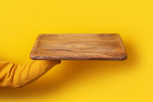 Wooden Kitchen Tray In Hand Over Yellow Background