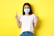Leinwandbild Motiv Covid-19, pandemic and social distancing concept. Disappointed asian girl in medical mask, frowning upset and pointing fingers up at logo, standing over yellow background