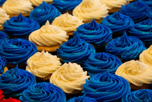 Table Covered With Cupcakes With Blue And White Cream Toppings