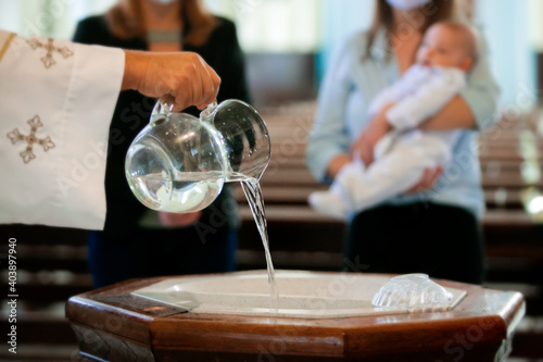 Fotografija Priest pouring holy water into the baptismal font, moments before a child receiv
