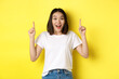 Leinwandbild Motiv Beauty and fashion concept. Beautiful asian woman in white t-shirt pointing fingers up, standing over yellow background