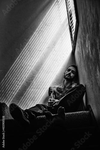 Fototapeta Portrait Of Shirtless Man Sitting Against Wall
