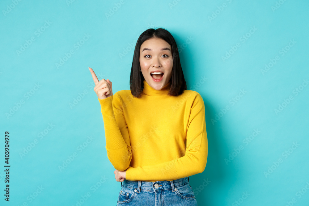 Leinwandbild Motiv - Mix and Match Studio : Shopping concept. Attractive korean woman smiling amazed, pointing finger left, showing good deal banner, standing against blue background