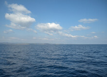 Calm Ocean With Glistening Water Under A Cloudy Sky