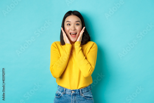 Fototapeta Portrait of pretty korean girl receive surprising news, looking amazed and happy