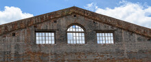 Panorama Of The Walls Of An Old Brick Building. Triangular Shape. Window Openings With Wooden Frames. Background - The Sky With Clouds. Ruins Concept.