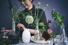 色々な花器に花を生ける女性