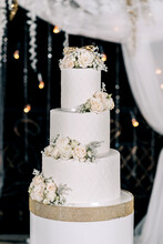 Wedding Cake White Three Tiers On A Dark Background With White And Yellow Roses With Gold Edging