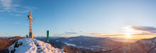 Cross On The Top Of A Mountain At Sunrise. Panoramic View From Above Of Lake Lugano In Winter With Snow, Italy. Below You Can See The Town Of Porto Ceresio