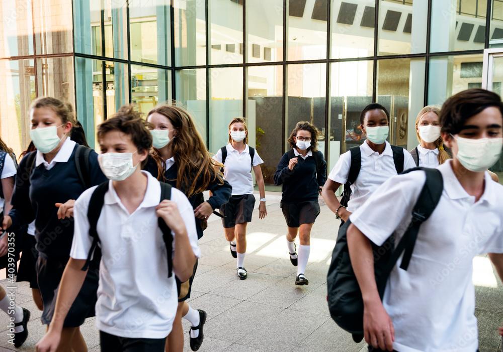 Fototapeta High school students wearing masks on their way home