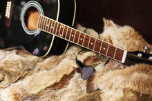Old Dusty Acoustic Cutaway Guitar On A Floor. Spruce Dreadnought Acoustic Guitar. Guitar On A Fur Background.