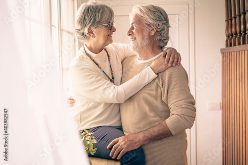 Fototapeta A moment of tenderness between two senior people who hug each other with love in front of the window, looking into each other's eyes